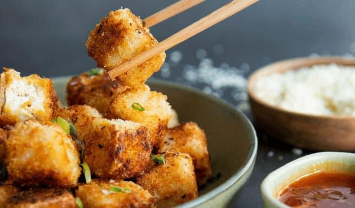 Bilden visar pankopanerad tofu lyfts upp med ätpinnar