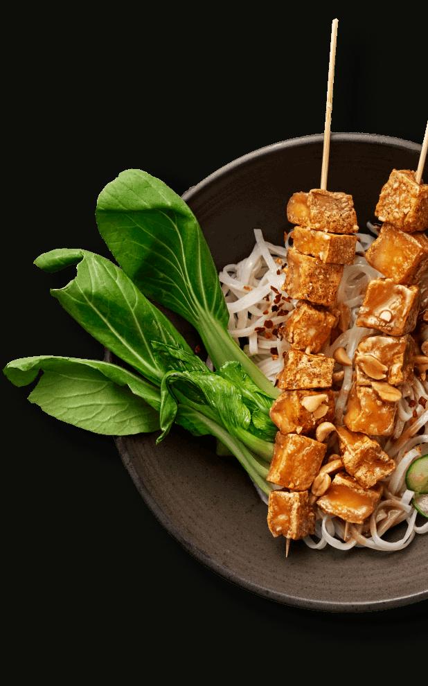 Bilden visar en tallrik med Yipin produkt: friterad tofu, pak choi och nudlar